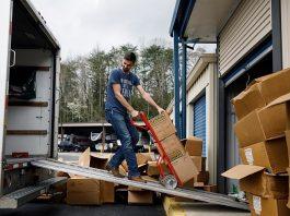 Noah Colvin vận chuyển các kiện hàng nước rửa tay mà hai anh em tích trữ được. Ảnh: NYT