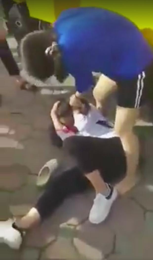 Em học sinh bị đánh chỉ biết nằm im chịu đòn, không thể phản kháng. (Ảnh cắt từ clip).