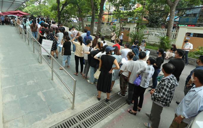 Người dân xếp hàng từ cổng Bệnh viện vào khu vực khai báo y tế ngày 22-7 - Ảnh: Ngô Nhung.